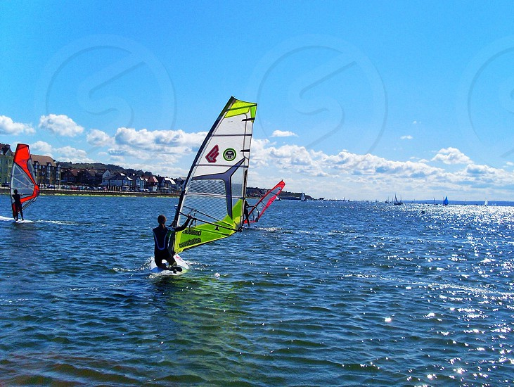three sail surfers on lake photo