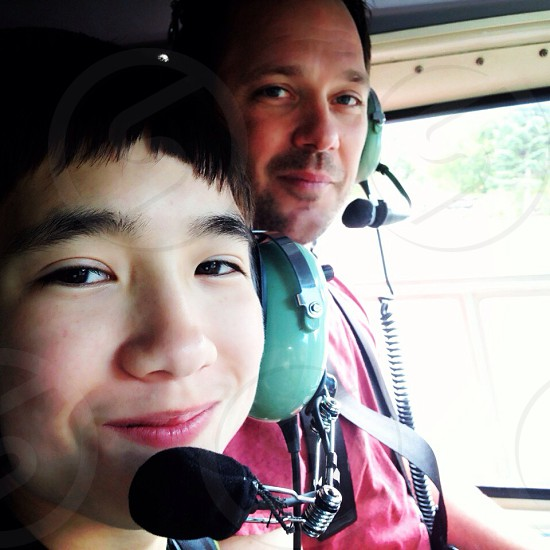 Family adventure helicopter ride headphones and microphones father and son bonding photo