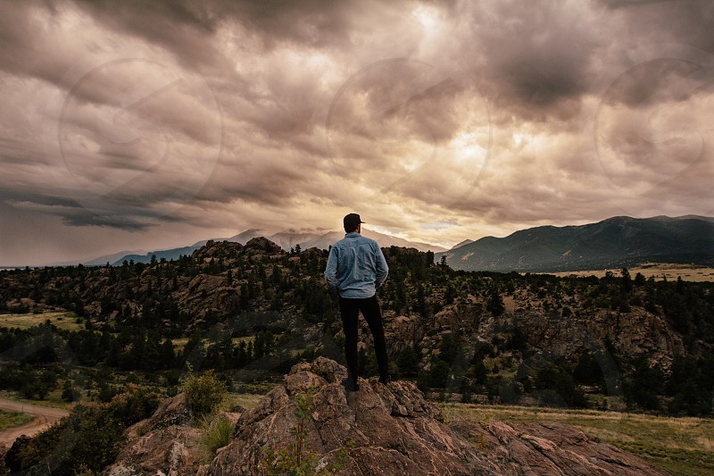 man with black short hair in light blue long sleeved dress shirt black pants and shoes standing on top of mountain photo