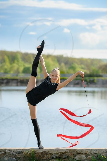 Smiling rhythmic gymnast is doing vertical split as a part of ribbon exercise. photo