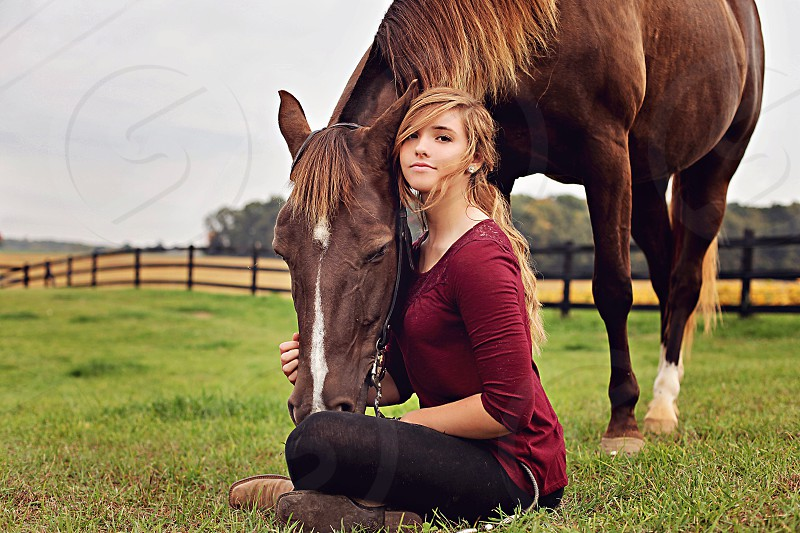 woman sitting on the grass with a brown horse photo