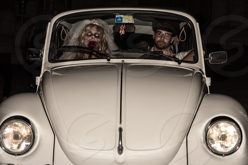 man driving a white volkswagen beetle with a zombie bridge riding beside photo