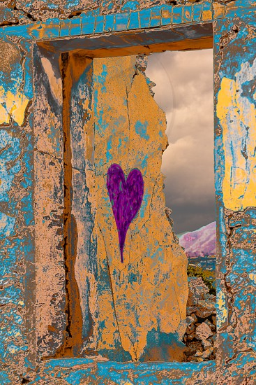 Symbol of love  purple heart graffiti on ruined wall of remains of old house photo