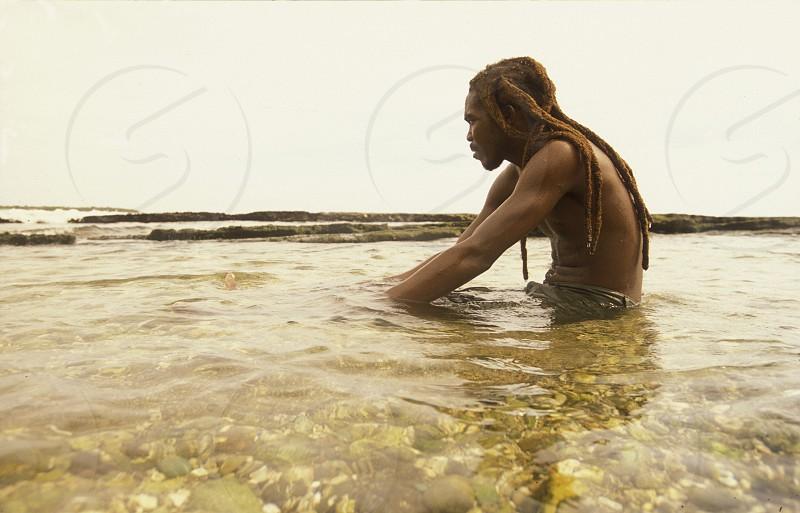 a men on a beach near the city of Santiago de Cuba on Cuba in the caribbean sea. photo