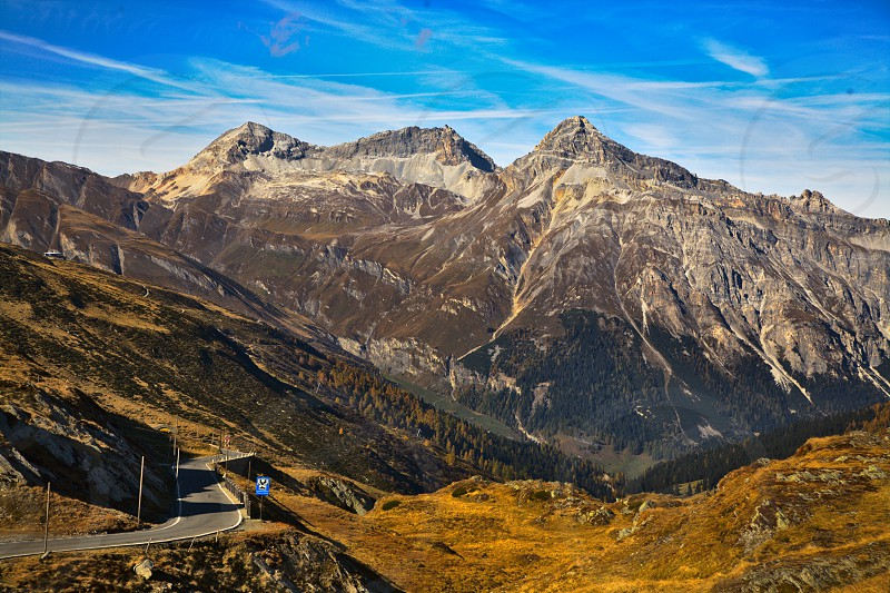 top of Splugen pass Switzerland / Italy. Beautiful scenery  mountauns  trees  grass and a road.  wonderful blue sky with clouds passing by. Details and shadows! photo
