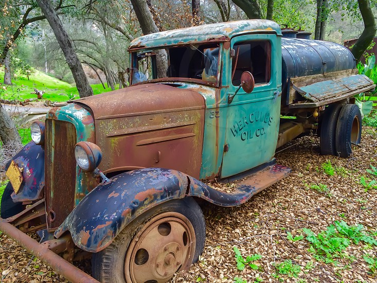 Antique rusty truck oil tanker in woods photo