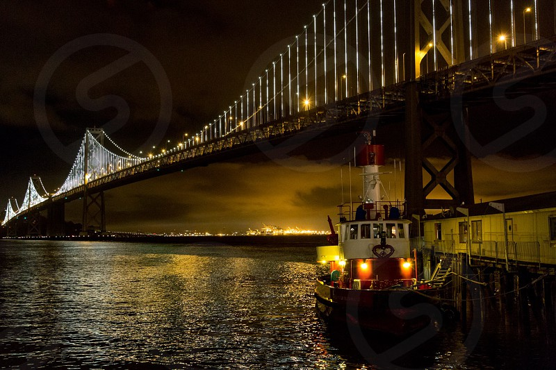 sailing boat below bridge with lights photo