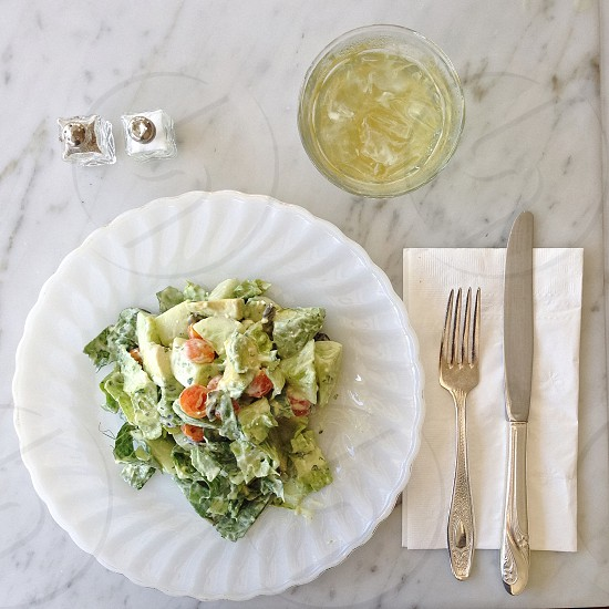 salad on plate with knife and fork and side and glass of drink on the upper right side photo