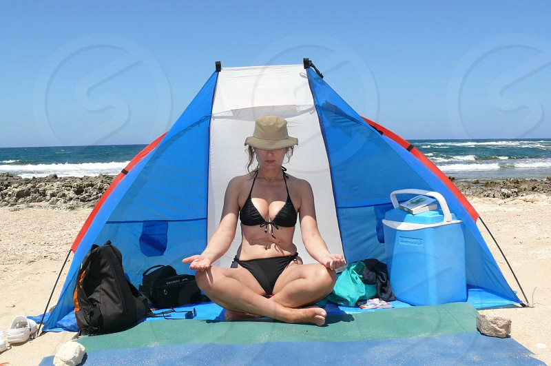woman meditating in a blue tent photo