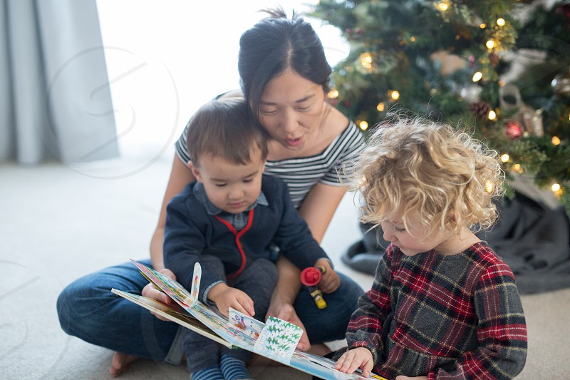 Toddlers reading with their mother photo