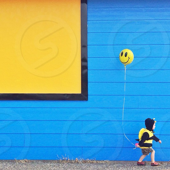 child in a bee costume holding a smiley balloon beside a blue building photo