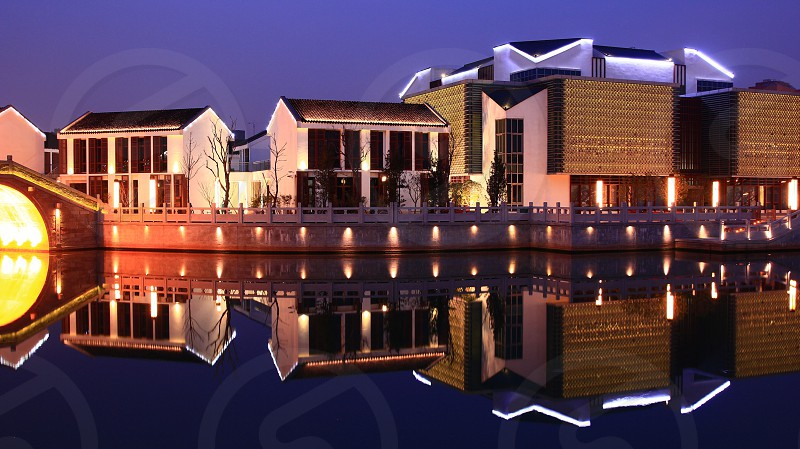 Illuminated buildings newly designed to match old style traditional chinese houses with reflection in the river Suzhou China Xietang Laojie photo