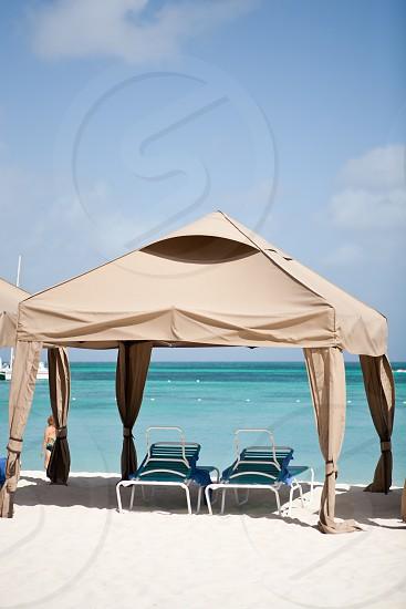Caribbean beach lounge chairs tent white sand. photo