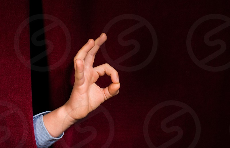 Hand symbol of success. Red curtain background photo