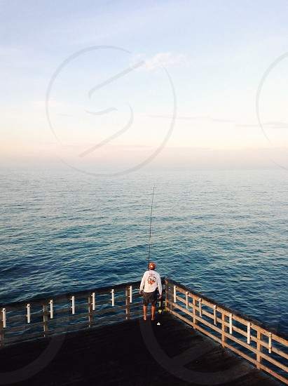 person fishing off pier photo