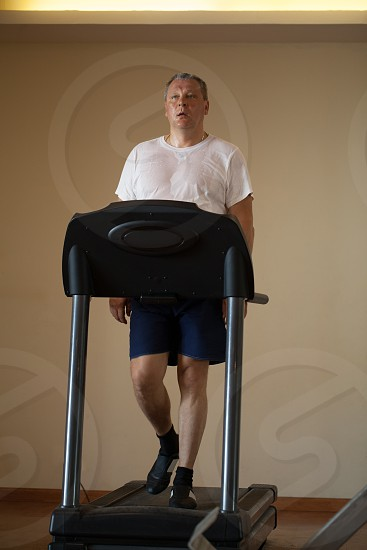 Fit attractive middle-aged man working out on a treadmill in a health and fitness concept photo