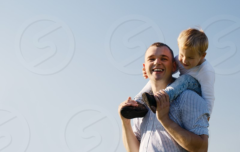 Young father giving his son a piggy back ride as the youngster sits on his shoulders laughing with enjoyment low angle against a blue sky with copyspace photo