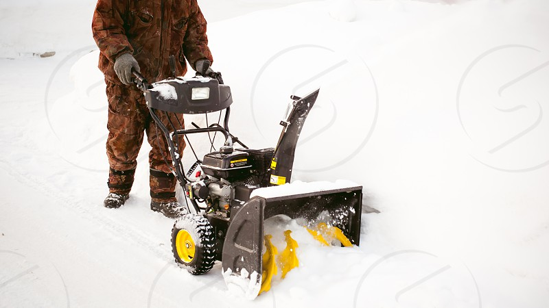 man operating snow blower to remove snow on driveway photo