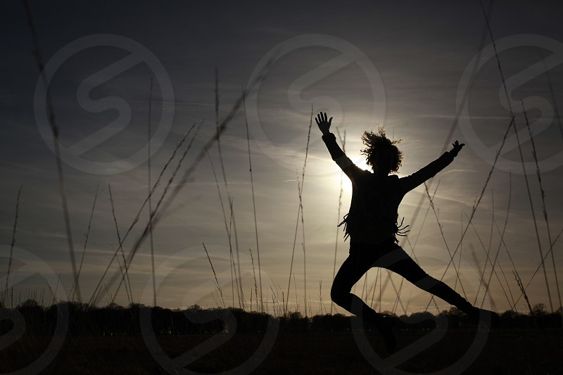 silhouette of scarecrow with arms wide open on field during golden hour photo