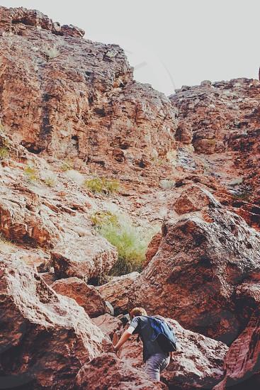 man climbing on brown rocks photo