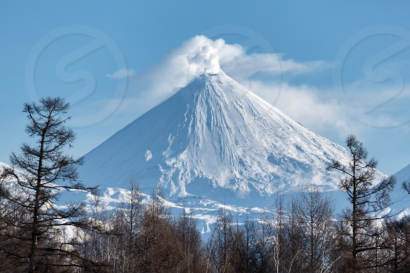Winter volcanic landscape of Kamchatka Peninsula: view of eruption active Klyuchevskoy Volcano in sunny day clear weather. Eurasia Russian Far East Kamchatka Region Klyuchevskaya Group of Volcanoes photo