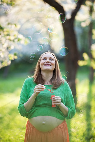 Cheerful young pregnant woman enjoying worry-free time in the park. She looking at flying bubbles on background of blurred nature scene on sunny day photo