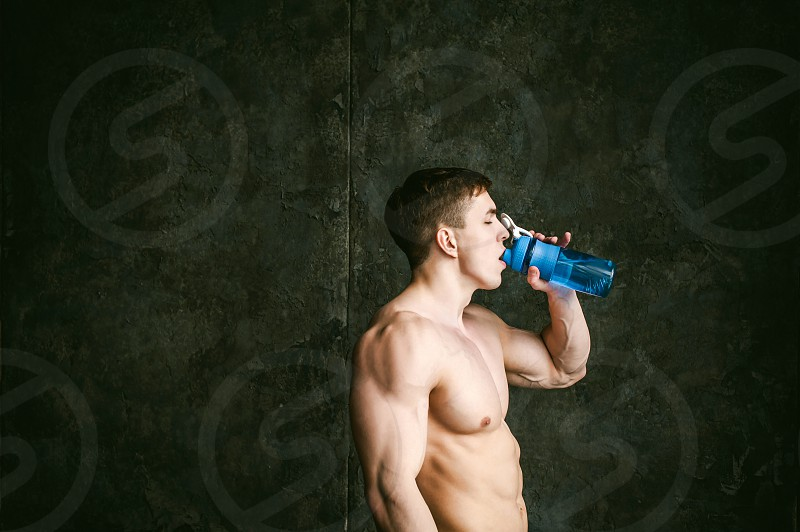 Young sexy men bodybuilder athletestudio portrait loft on background of stylized wallguy model With a bare torso Drinks water from a sports bottle of blue color after training photo