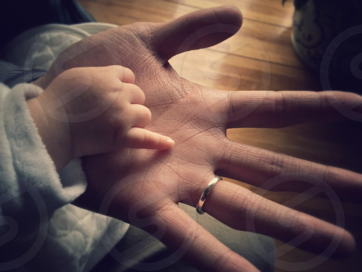 big palm with silver wedding band holding baby's hand with pinky out photo