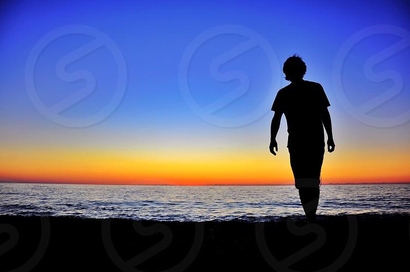 man silhouette walking on sea shore photo
