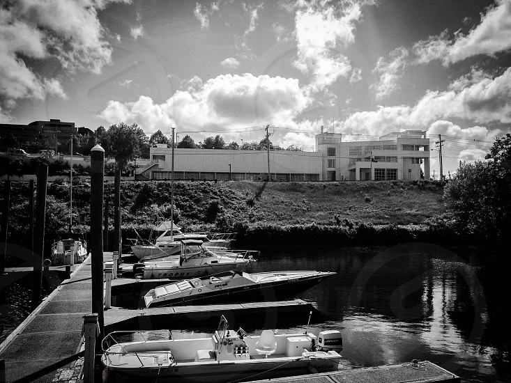 motorboats and speedboats docked in grayscale photo