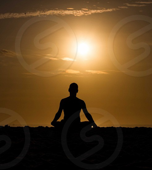 silhouette of person doing yoga during sunset photo