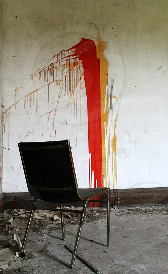 black and silver chair in front of red yellow and white painted wall photo