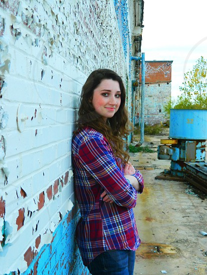 woman in white blue and red plaid flannel shirt leaning on wall photo