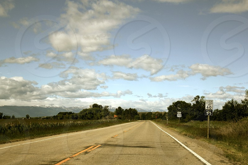 Hard and soft clouds and road mountain speed limit sign photo
