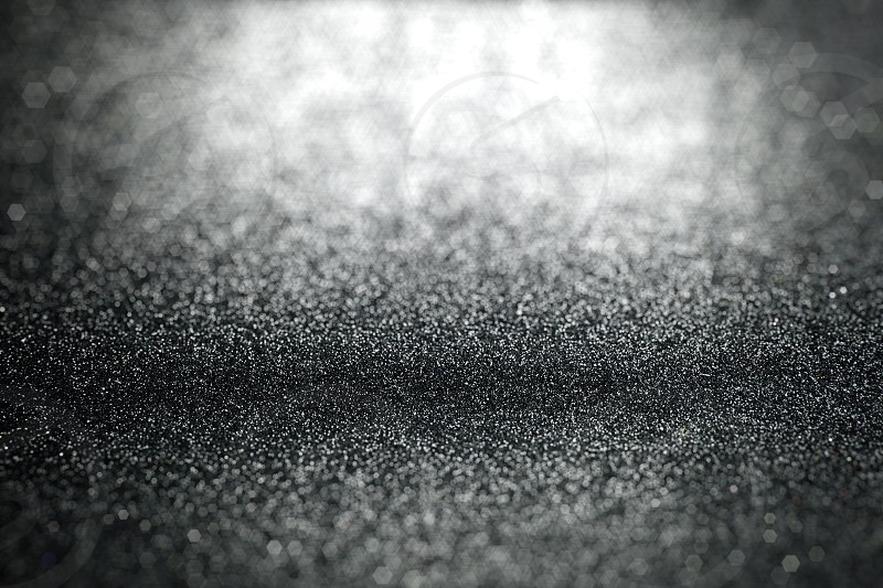 Abstract black glitter background with surface texture focused and blurry bokeh area in foreground and background photo