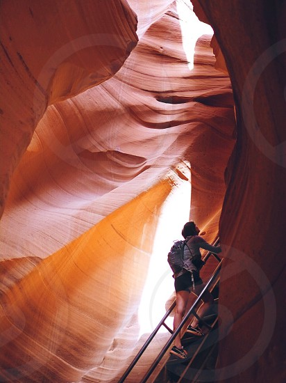 man walking up metal staircase in middle of red rocky canyon photo