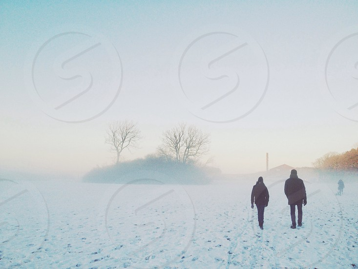 two person walking on snowy area under bright sky during daytime photo