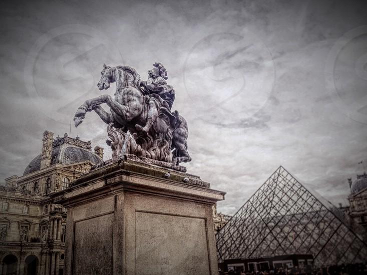horseman statue near building under gray clouds photo