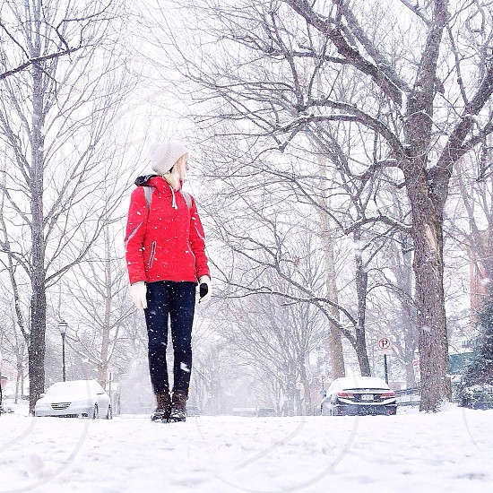 woman in red jacket and blue pants standing in a snowy street photo