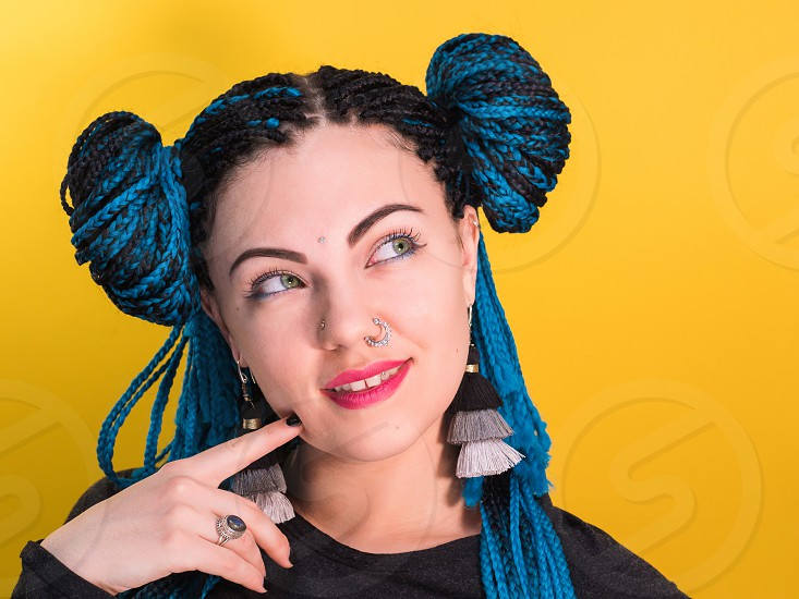 Glamour pensive portrait of sexy woman with african blue braids hairstyle bindi nose ring and tassel earrings isolated on yellow background. Hipster girl wondering. photo