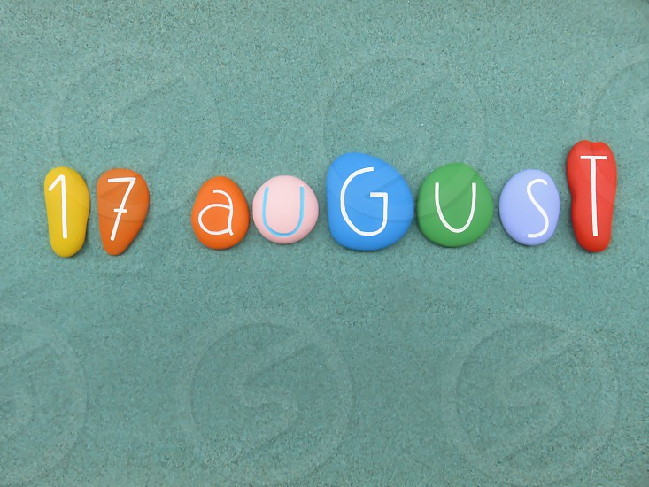 17 August calendar date composed with multi colored stones over green sand                             photo