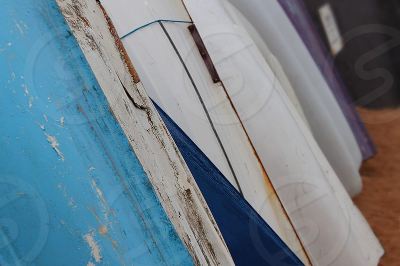 Photograph of the colourful weathered hulls of boats stacked up along Broadstairs' harbour wall. photo