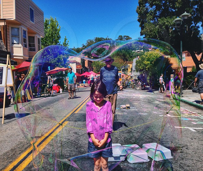 girl in purple button up long sleeved shirt inside bubble photo
