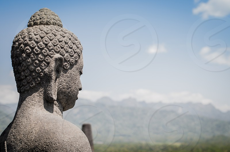 A statue of Buddha overlooking a mountains in Borobudur temple Central Java Indonesia photo