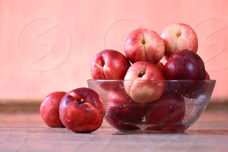red and white peaches in clear glass bowl photo