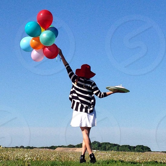 woman in black and white stripe shirt walking holding balloons photo