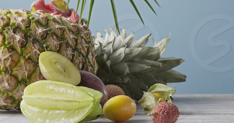Ripe fresh organic pine apple with natural exotic fruits and palm evergreen leaves on a wooden table on ablue background. Vertical panoramic motion 4K UHD video 3840 2160p. photo