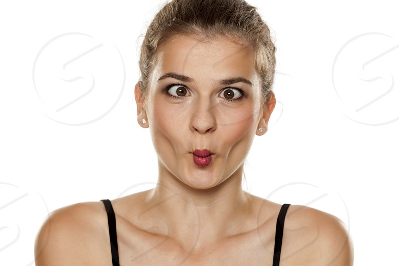 Portrait of beautiful young woman making fish face on white background photo