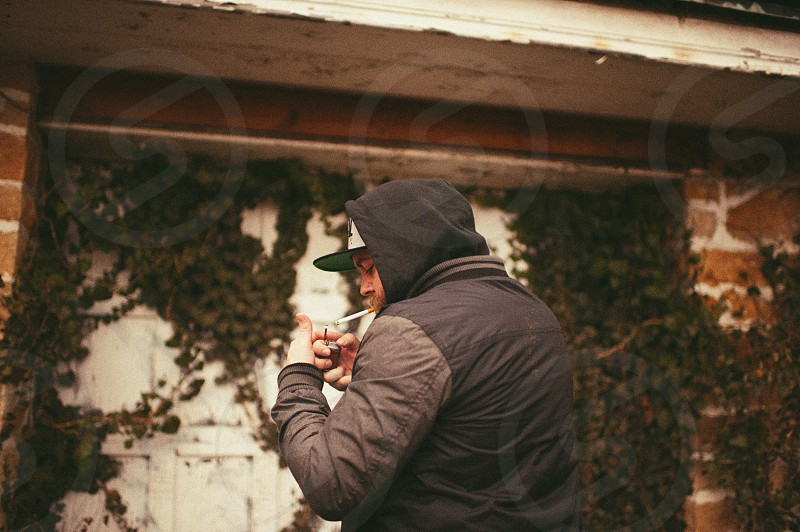 man in grey black hoodie white baseball hat lighting a cigarette photo