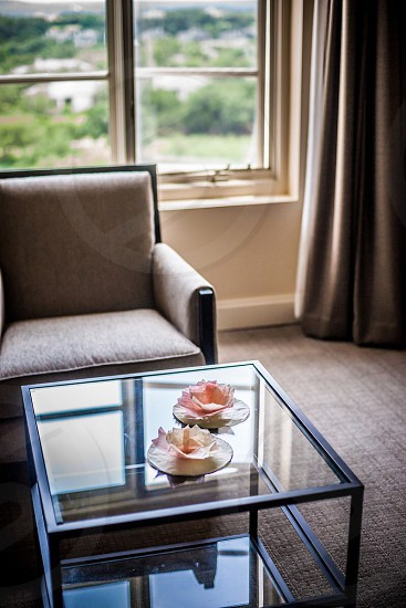 glass coffee table beside a padded chair photo